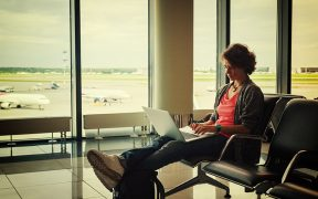 Image of a woman working on her laptop sitting in an airport for Canada and the Changing Nature of Work blog post