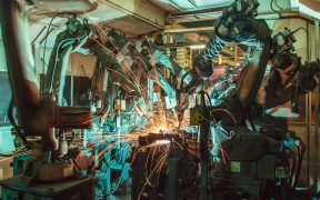 Image of robots welding in a factory for Robots as a Social Solution or a Social Disruption in Asia blog post