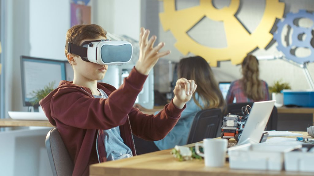 Image of a boy in a classroom wearing virtual reality goggles for The Future of Learning and Training Environmental Scan blog post