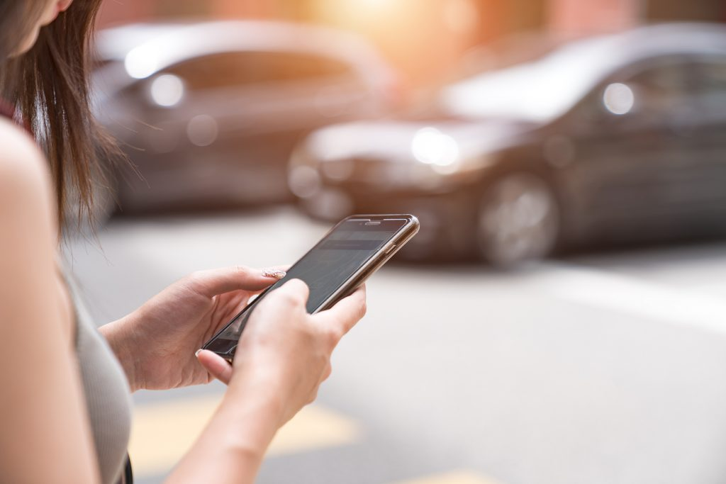 Image of a woman using her smartphone with a parked car in the background for Google Has Launched the First Ride Hailing Price Comparison Tool, That Include Uber and Lyft blog post