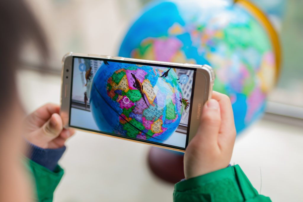 Child using phone to look at globe to play augmented reality game