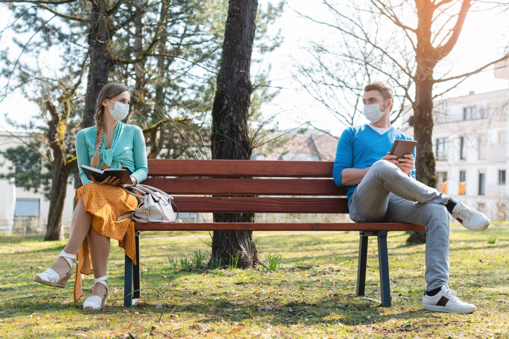 Woman and man wearing face masks and socially distancing on a park bench while reading