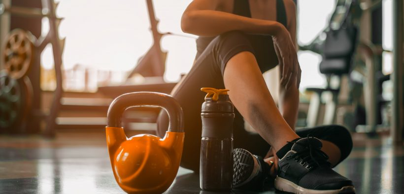Woman sitting on a gym floor with fitness equipment around her.