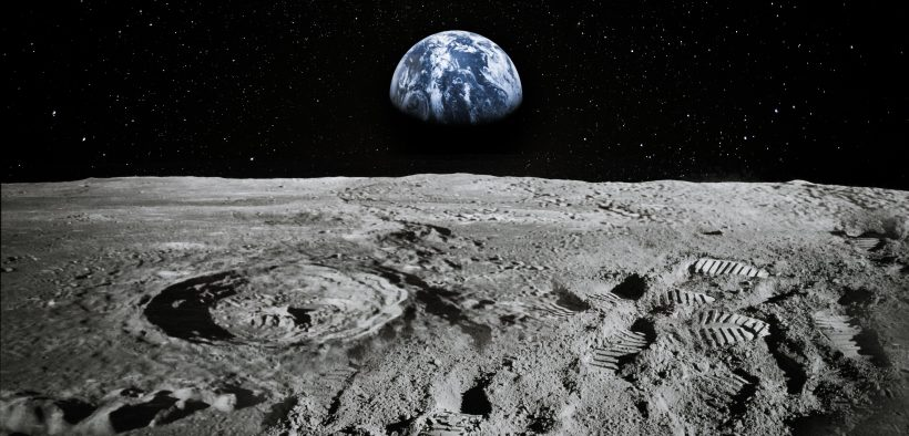 Surface of the moon with the earth rising on the horizon.
