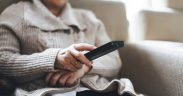 Elderly person holding television remote